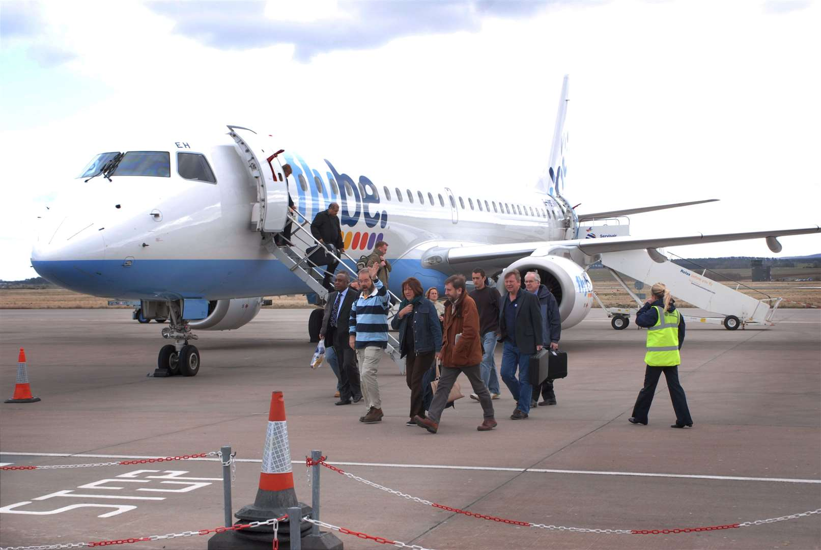 Passengers arrive at Inverness Airport on a a Flybe jet.