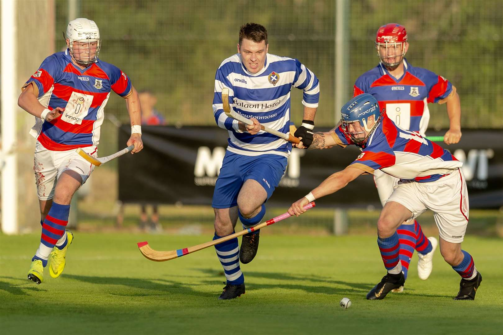 Newtonmore's Steven Macdonald is challenged by James Falconer (Kingussie) in the evening sunshine.